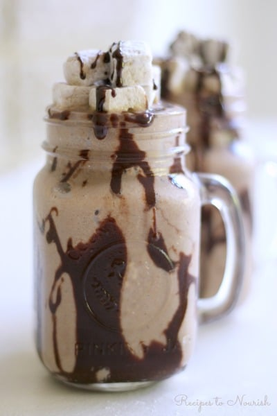 Frozen Hot Chocolate is a super fun treat on a hot summer day. Icy cold, chocolaty, creamy goodness mixed with healthy, whole food ingredients, topped with rich chocolate fudge sauce and homemade marshmallows is sure to please. | Recipes to Nourish
