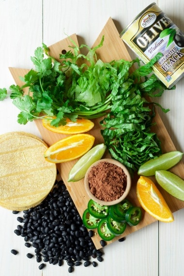 (Ad) These healthy and hearty vegetarian black bean tacos are stellar! They're deeply flavored with hints of sweet orange and chocolate, spicy cumin and jalapeños, and packed with creamy black beans, sweet corn and salty olives. | Recipes to Nourish