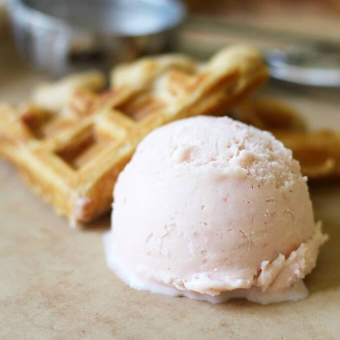 Scoop of watermelon ice cream with homemade waffles.