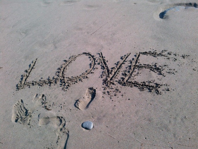 Beach sand with the word LOVE traced in it.