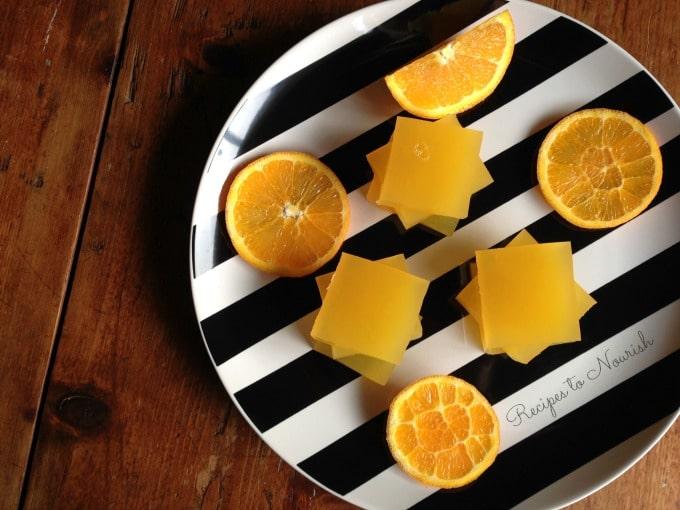 Orange jello squares on a plate with orange slices.