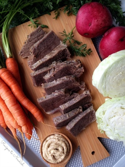 Slices of corned beef on a cutting board with carrots, cabbage, red potatoes and Dijon mustard.