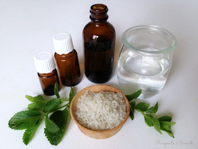 Amber essential oil bottles, a small glass of water, sea salt and fresh herbs.