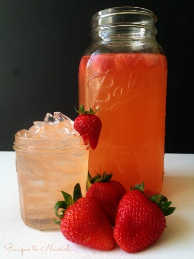 Strawberry Ginger Switchel in a mason jar and served over ice with fresh strawberries.