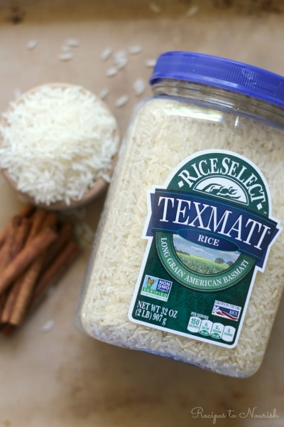 Container of RiceSelect Texmati rice and a bowl of white rice and cinnamon sticks.