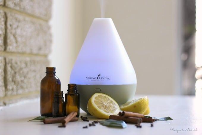 Essential oils, essential oil diffuser an lemons, herbs and cinnamon sticks.