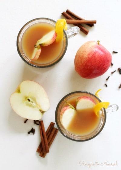 Glass mugs full of apple cider with apple slices, orange zest, cinnamon sticks and cloves.