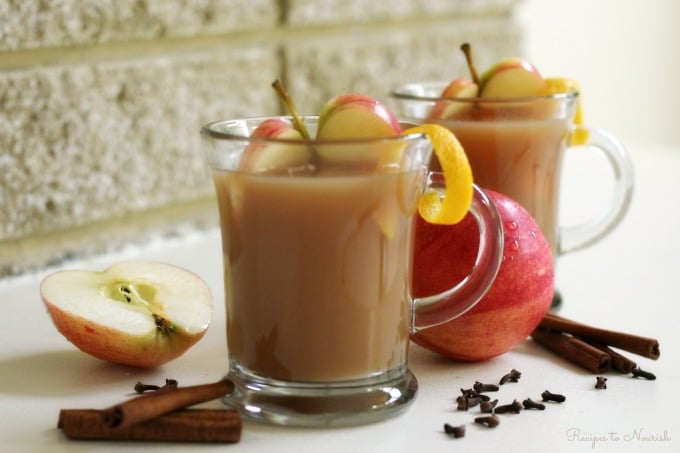 Glass mugs full of homemade apple cider with apple slices, orange zest, cinnamon sticks and cloves.