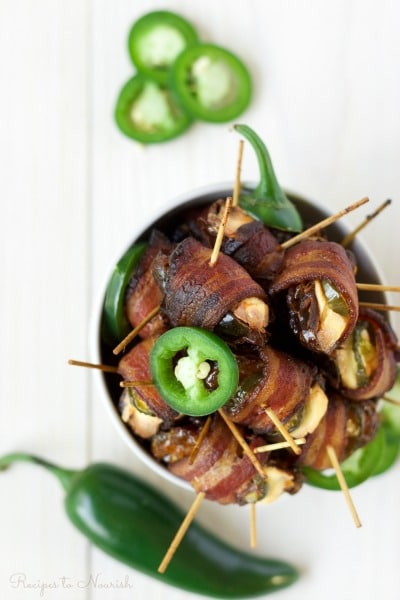 Bowl of bacon wrapped dates stuffed with cream cheese and jalapeño slices.