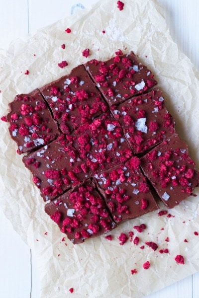 Chocolate Freezer Fudge is so easy to make! This creamy, delicious, chocolatey perfection is topped with sweet, crunchy freeze-dried raspberries and flaked sea salt. It has a special nourishing protein boost too! | Recipes to Nourish