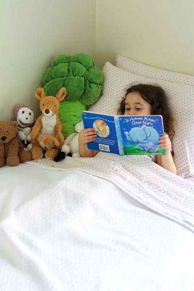 Little girl looking at a children's book in her bed with her stuffed animals.