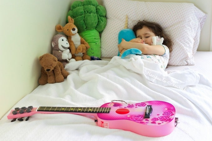Little girl in her bed hugging her stuffed animals with her pink guitar sitting on the bed.