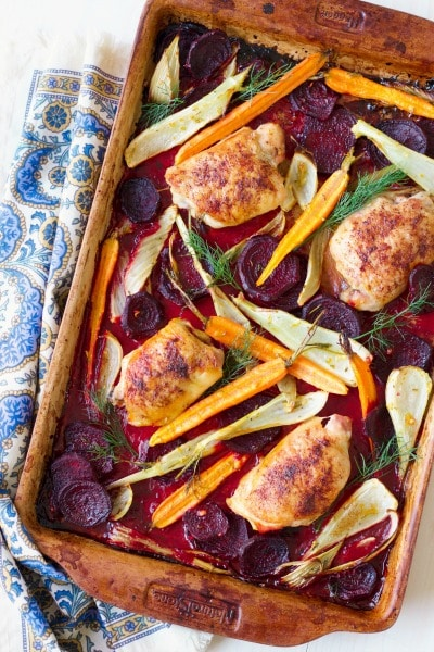 Roasted chicken thighs on a pan with roasted beets, carrots and fennel.