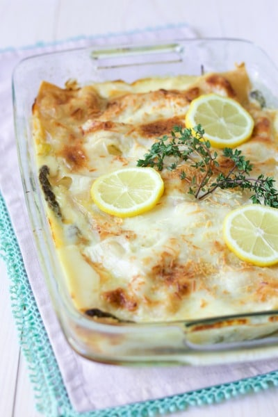 Creamy white sauce lasagna with cheesy top, fresh lemon slices and fresh thyme.