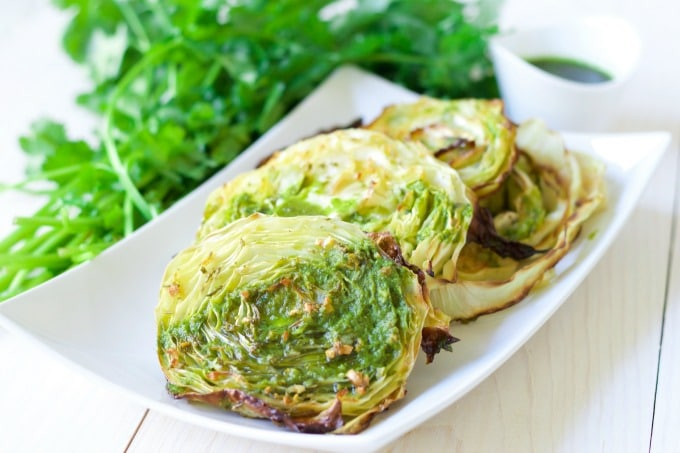 Roasted cabbage steaks on a plate with chimichurri sauce drizzled over the top and fresh cilantro on the side.