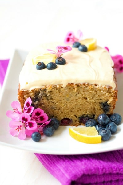 Frosted loaf cake with a slice cut off with fresh blueberries, lemon slices and geranium flowers.