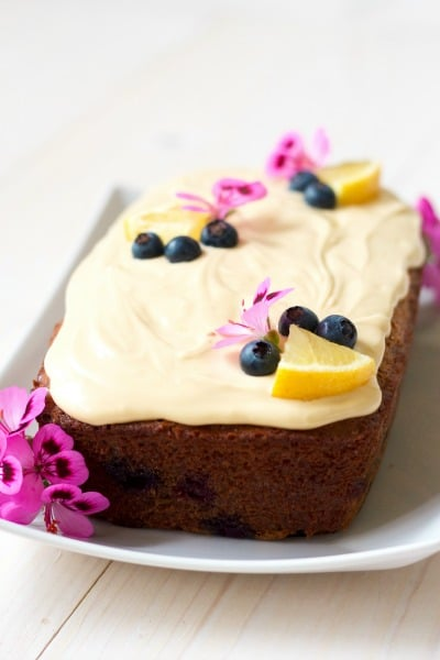 Frosted loaf cake with fresh blueberries, lemon slices and geranium flowers.