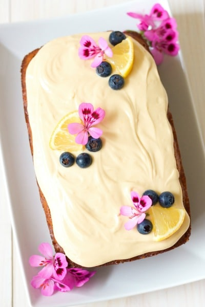 Overhead view of frosted loaf cake with fresh blueberries, lemon slices and geranium flowers.