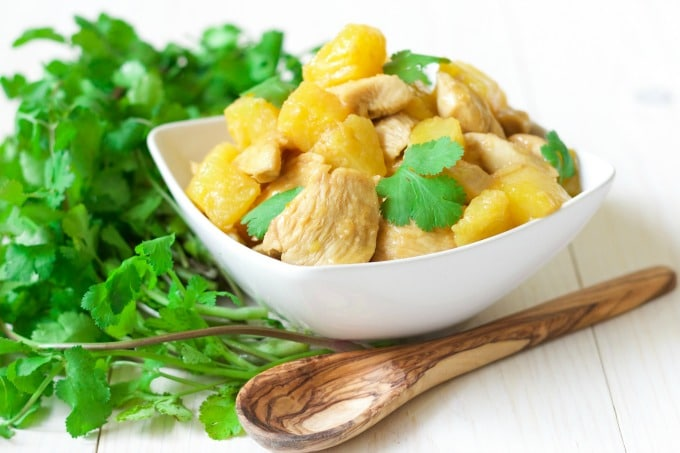 Pineapple chicken with fresh cilantro in a bowl with a wooden spoon next to it.