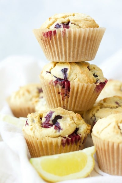 3 blueberry muffins stacked on top of each other surrounded by more muffins and fresh lemon slices.