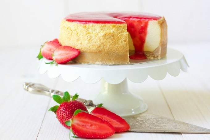 Whole cheesecake with a slice cut out with strawberry sauce on the top and fresh strawberries.