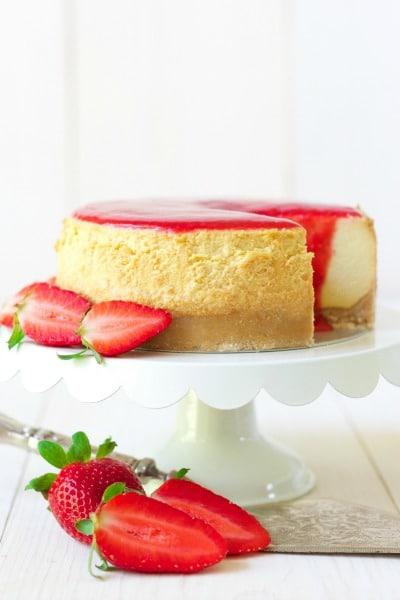 Whole cheesecake with a slice cut out and strawberry sauce on the top with fresh strawberries.