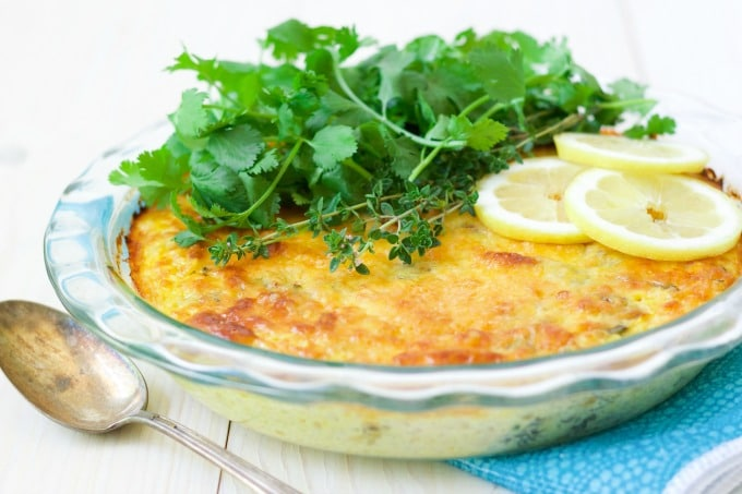 Breakfast casserole topped with fresh herbs and lemon slices.