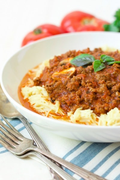 (Ad) Overflowing with seasonal tomatoes, this hearty Summer Bolognese gluten free spaghetti is sure to please. This classic, simple meat-based ragù sauce is brimming with summer produce and is pure comfort food when served over gluten free spaghetti, zoodles or spaghetti squash. | Recipes to Nourish