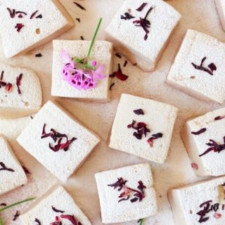 Square-cut homemade marshmallows with dried hibiscus and pink flowers.