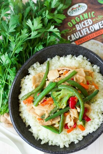 (ad) Thinly sliced chicken stir-fried with frozen vegetables and topped on riced cauliflower is so easy to make! This budget-friendly, Frozen Vegetable Asian ChickenStir Fry Cauliflower Bowl is packed with a sweet gingery flavor and whips up in 15 minutes, making it a perfect weeknight meal. | Recipes to Nourish