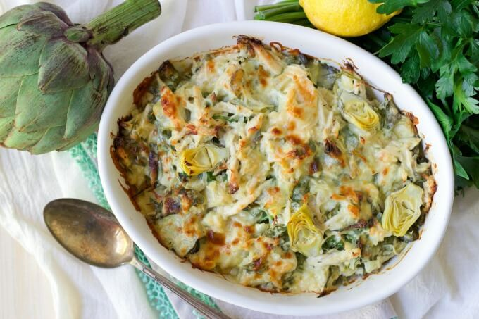Healthy Spinach Artichoke Chicken Casserole with fresh lemon, artichoke and parsley.