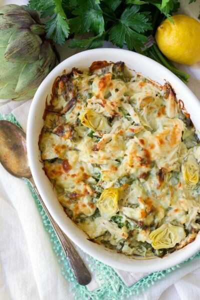 Healthy Spinach Artichoke Chicken Casserole with fresh lemon, parsley and artichoke.