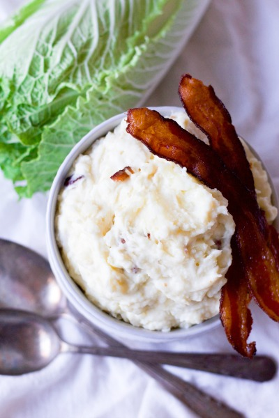 Mashed potatoes with two slices of crispy bacon and green cabbage.