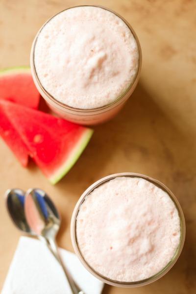 Watermelon milkshakes in 2 mason jars with fresh watermelon slices.