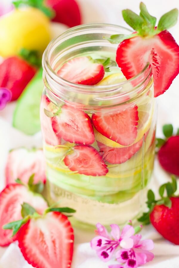 Mason jar filled with water, strawberries, lemon slices and cucumber slices.