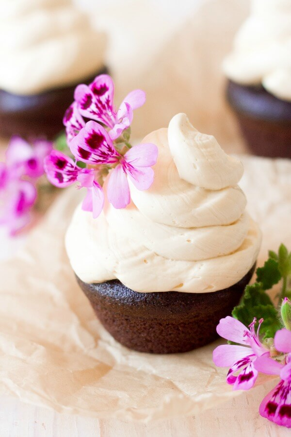 Vanilla buttercream frosting on top of chocolate cupcakes with pink flowers.