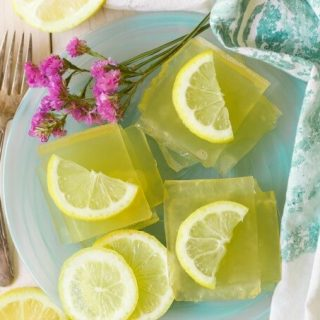 Square slices of homemade lemon jello with lemon slices.