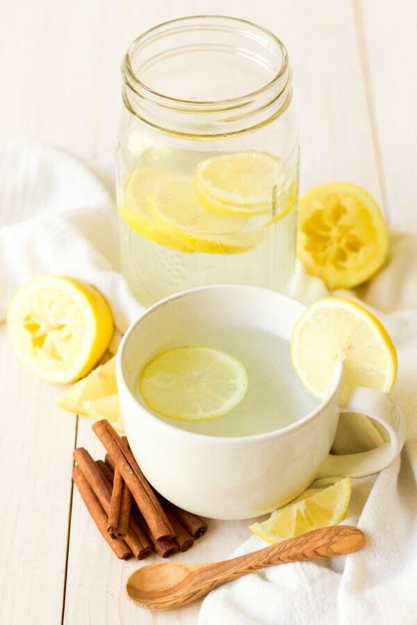 Mug and mason jar full of hot drink and lemon slices, next to lemons and cinnamon sticks.