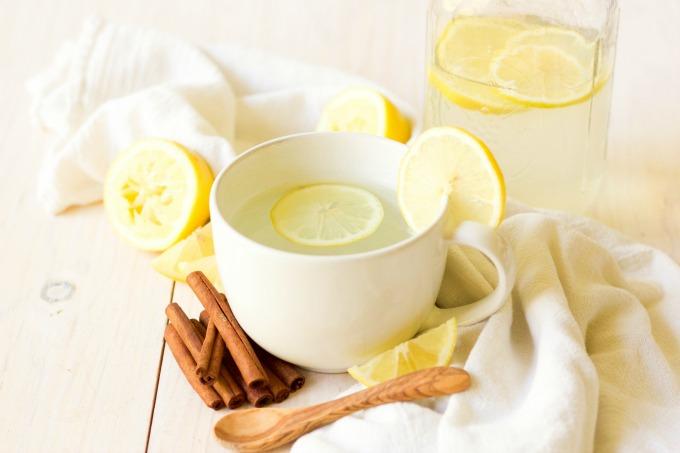 Mug and mason jar full of hot drink and lemon slices next to lemons and cinnamon sticks.