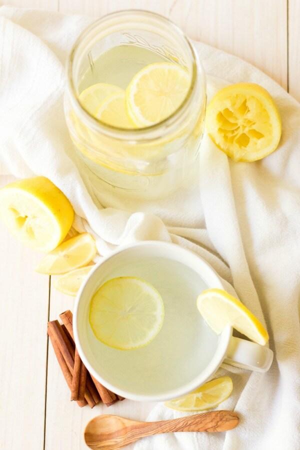 Mason jar and mug with hot drink and lemon slices with cinnamon sticks.