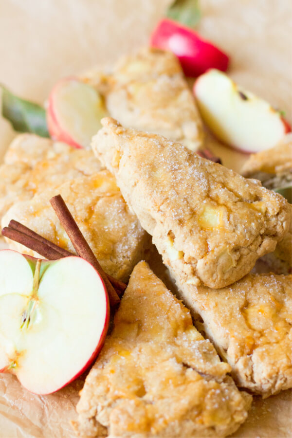 Stack of apple scones with fresh apples and cinnamon sticks.