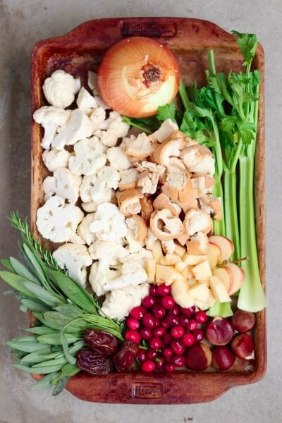 Baking sheet with celery, bread cubes, cauliflower, onion, cranberries, fresh herbs, dates and chestnuts.
