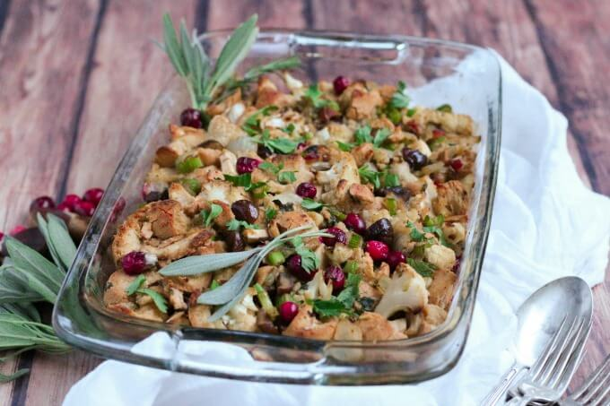 Casserole dish full of stuffing, cranberries and fresh sage.