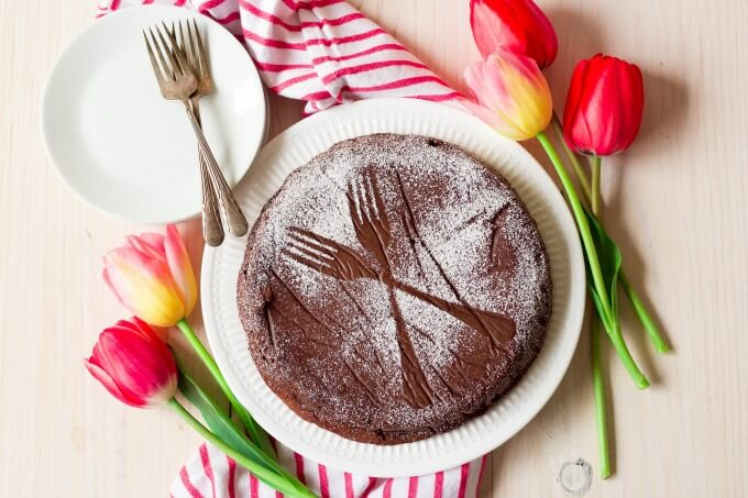 Chocolate torte cake dusted with powdered sugar making two forks pattern next to tulips.