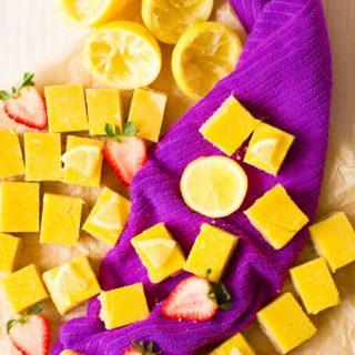 Homemade lemon squares with fresh lemon and strawberries.