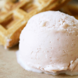 Big scoop of ice cream with homemade waffles.