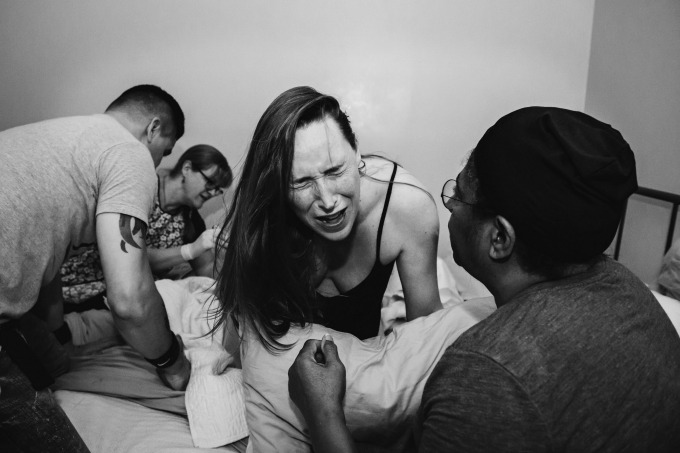 A mother in pain in active labor on her bed during a home birth surrounded by her husband and birth team.