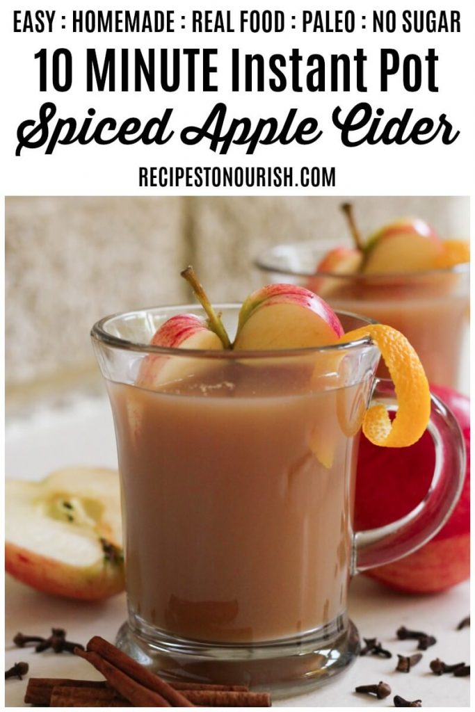 Glass mugs filled with spiced apple cider, fresh apple slices, orange peel, cinnamon and cloves.