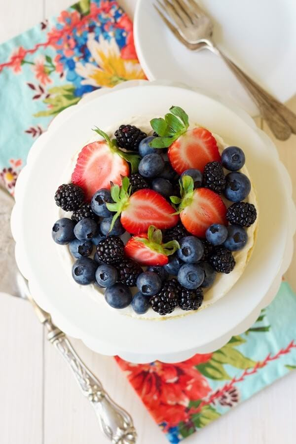 Overhead view of a cheesecake tart topped with fresh blueberries, strawberries and blackberries sitting on a cake stand.