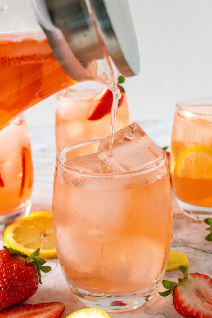Glass pitcher pouring a strawberry drink into a glass filled with ice next to more glasses that are filled with the strawberry drink, ice, sliced lemons and sliced strawberries.